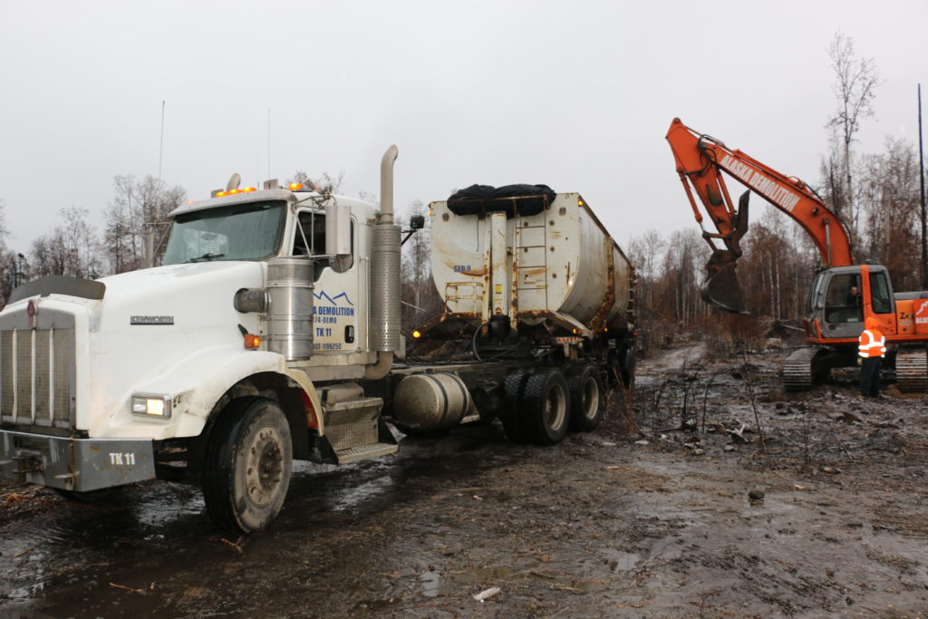 semi truck with excavator loading debris for salvage
