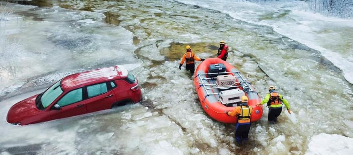 Icy, flooded road with partially submerged car and water rescue team transporting pets